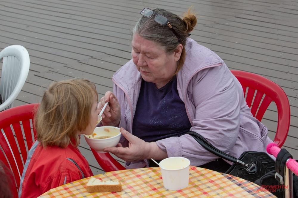 Бабушка кормит внучку главным угощением Дня рыбака.