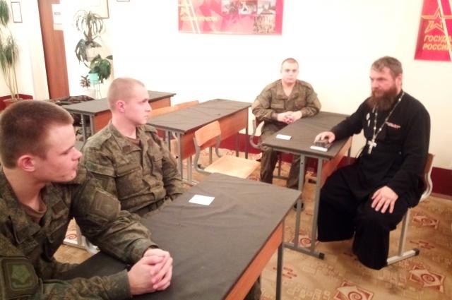 Молодые военнослужащие обсуждают с батюшкой и дела житейские.
