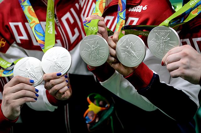 Серебряные олимпийские медали в руках российских гимнасток.