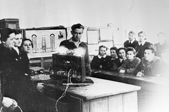 Алексей Леонов в школе на уроке физики демонстрирует прибор собственной конструкции. 1953 г.