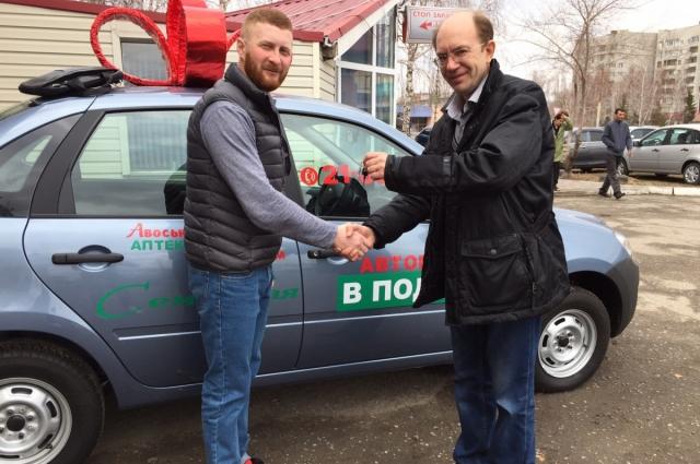 Управляющий сети аптек Сергей Никитин (справа) вручает ключи от Lada Granta Виктору Головко.