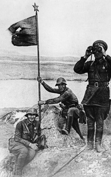Советские солдаты устанавливают боевой красный флаг на высоте Заозёрной