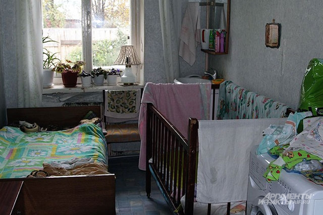 В комнате стоят стиральная машина, унитаз, гладильная доска и детская кроватка