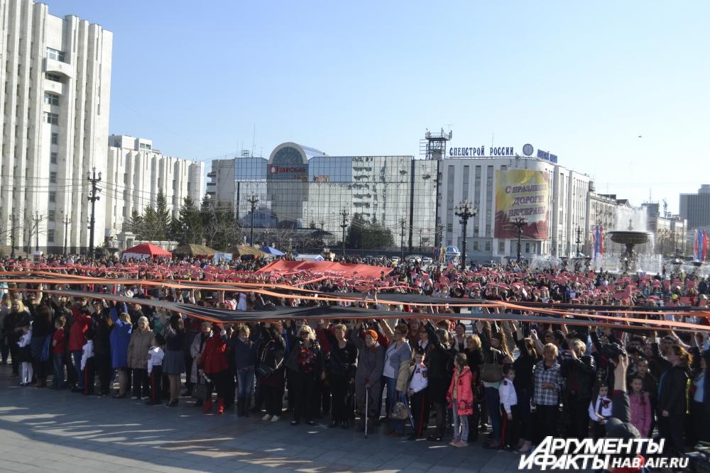 Хабаровчане развернули Георгиевскую ленты, Знамя Победы и флаг Российской Федерации.