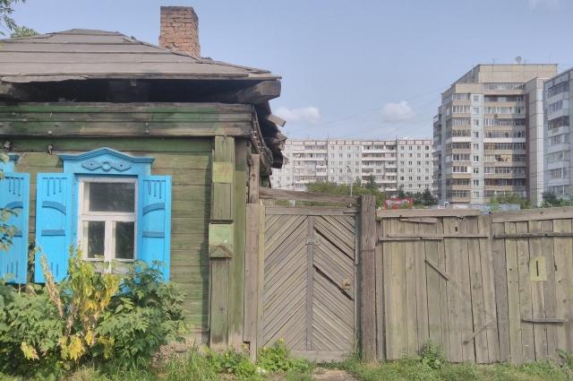 Типичный для сибирского города контраст: частный дом с печной трубой в окружении многоэтажек.