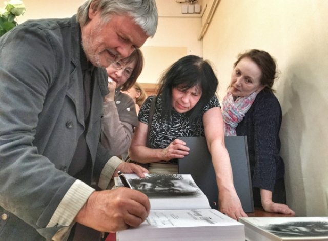 Вячеслав Михайлов подписывает подаренные библиотеке на Конной книги со своими рисунками.