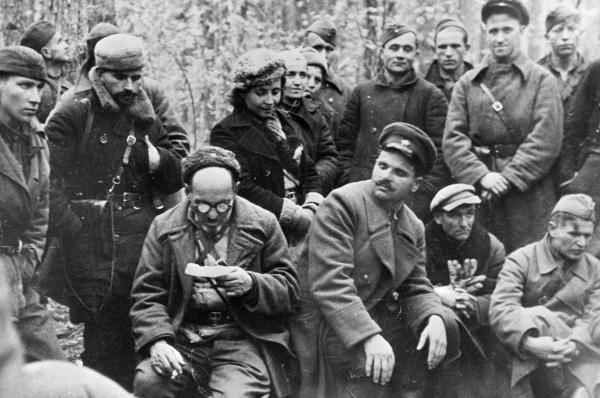 Ковпак (сидит слева) зачитывает партизанам шифровку с Большой земли. Комиссар отряда С. В. Руднев (сидит справа), 1942 г