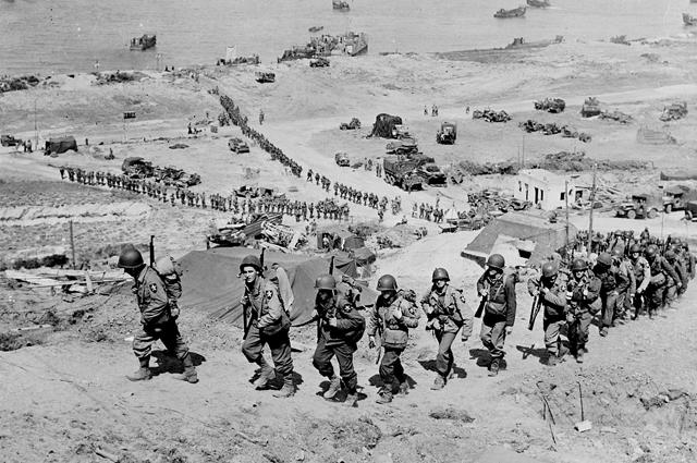 Американские солдаты, высадившиеся на пляже Омаха, продвигаются вглубь континента.