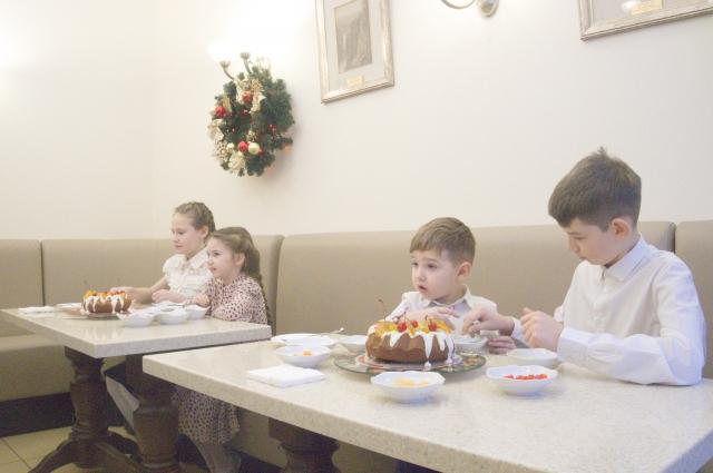 Ребятишки украсили праздничный пирог кусочками фруктов и сладостями.