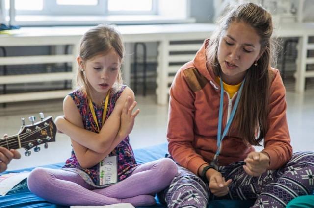 Мария Ковбаснюк учит ребят играть на гитаре.