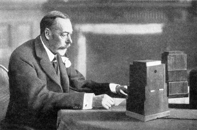 Король Георг V перед микрофоном произносит рождественское послание.
