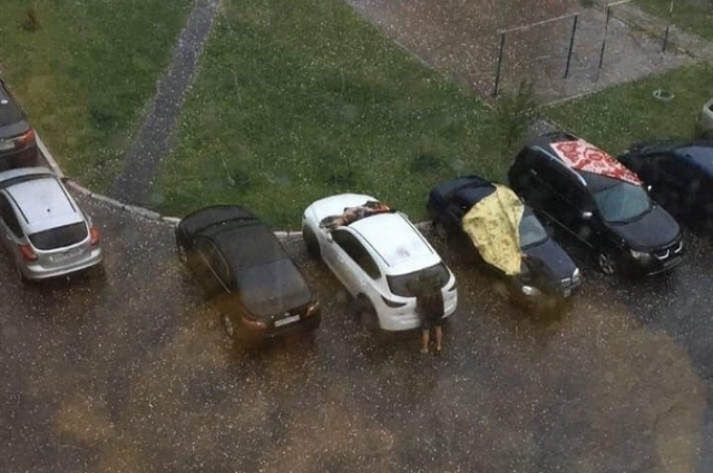 Люди стараются закрыть автомобили, чтобы их не побило градом.