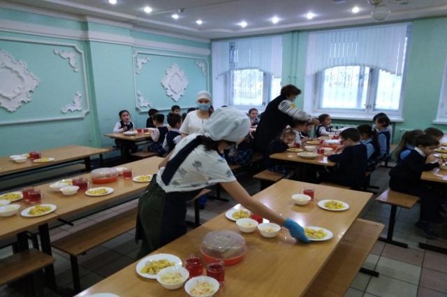 Пока ест один класс, дежурные на другой половине зала накрывают столы для других ребят.