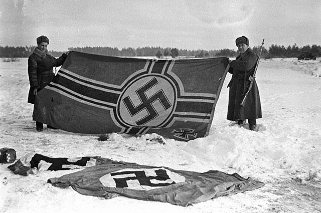 Красноармейцы демонстрируют первые немецкие знамена, захваченные в боях за освобождение города Калинина.