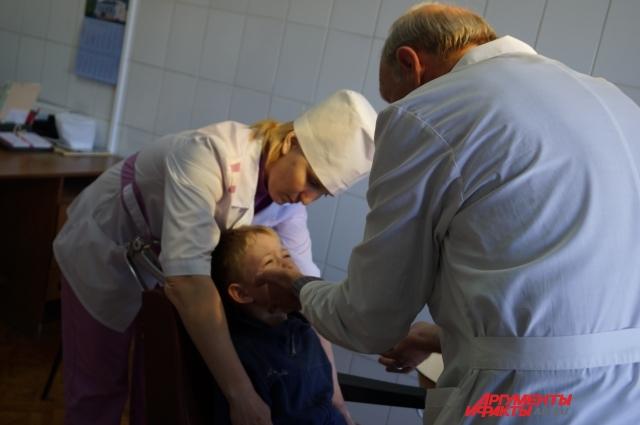 Чтобы ребёнок не мешал работе врача, медсестра придерживает его руки