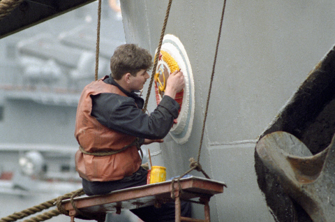 Матрос обновляет красками герб СССР на корме корабля Черноморского флота. 1992 г