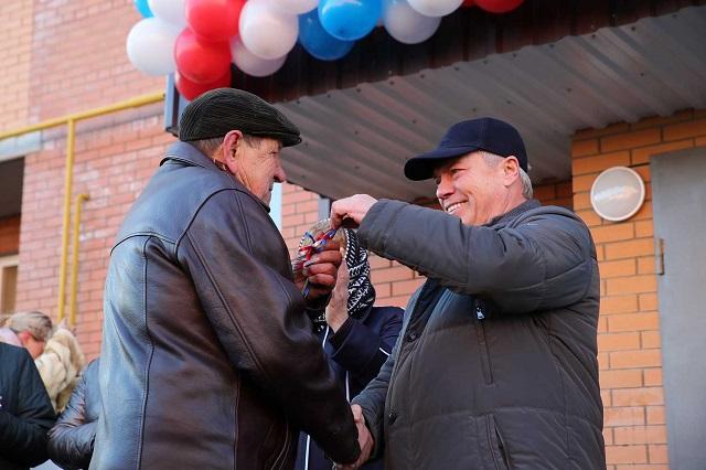 Губернатор Василий Голубев вручает ключи от квартир.