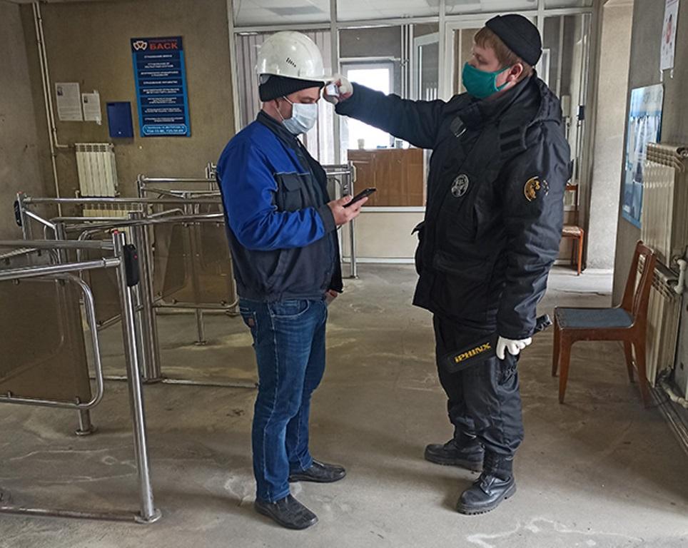 На входе у рабочих измеряют температуру.