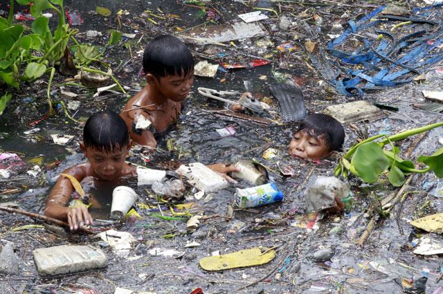 Плавать в реке, полной пластиковых отходов, -  малоприятное удовольствие. Пригороды Манилы (Филиппины).