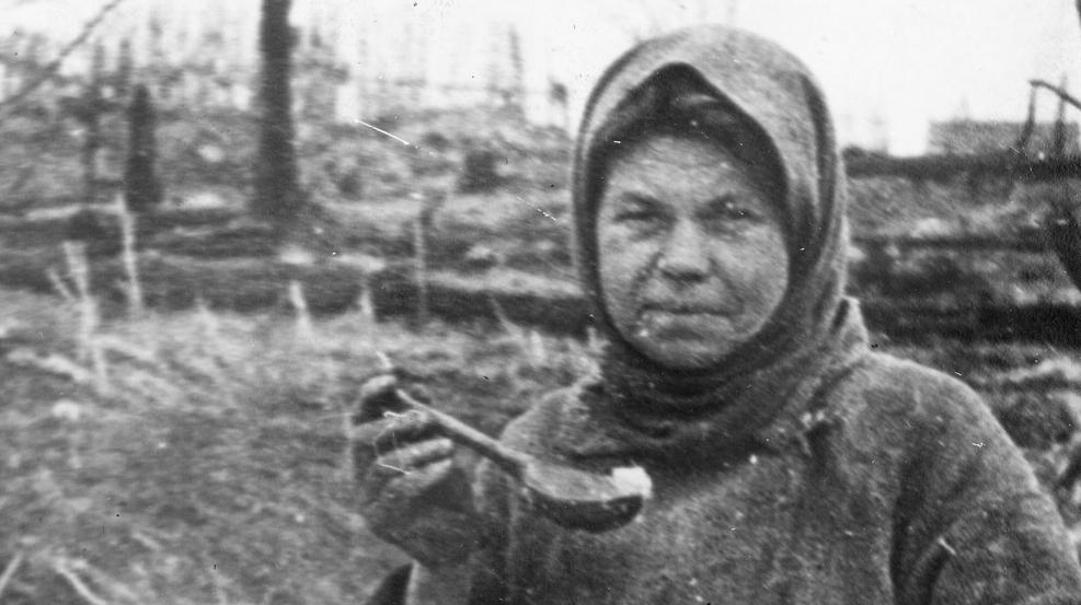 Жительница дер. Мамоново Батуринского района Е.О. Орлянова на пепелище своего дома, сожженного фашистами. Март 1943 г.