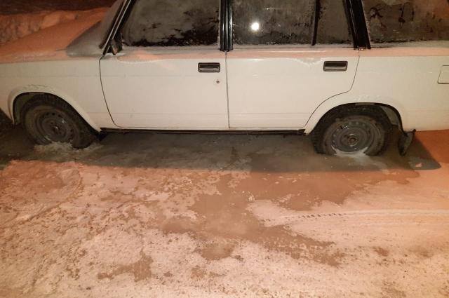 Пара автомобилей на стоянке всё ещё стоят во льду.