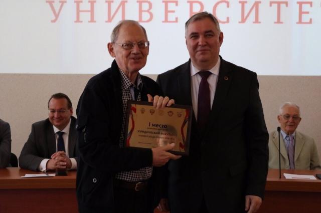 Ректор ПГНИУ Игорь Макарихин награждает Сергея Михайлова дипломом за победу студентов юрфака по итогам Универсиады.