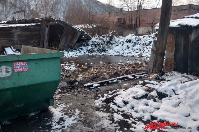 Местные жители сливают нечистоты в огромную лужу возле мусорки.