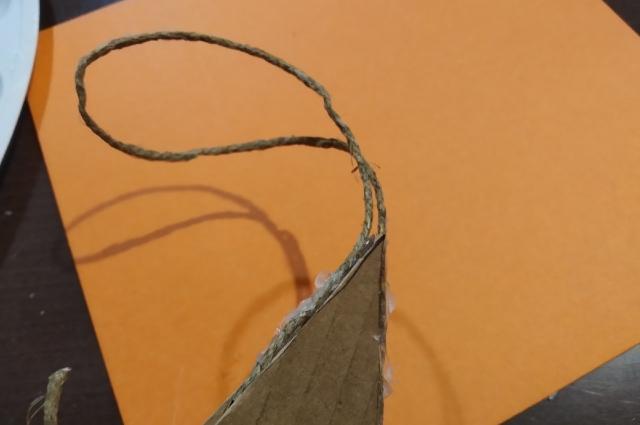Лучше клеить петельку по бокам картона, чтобы она не топорщилась под слоем шпагата.