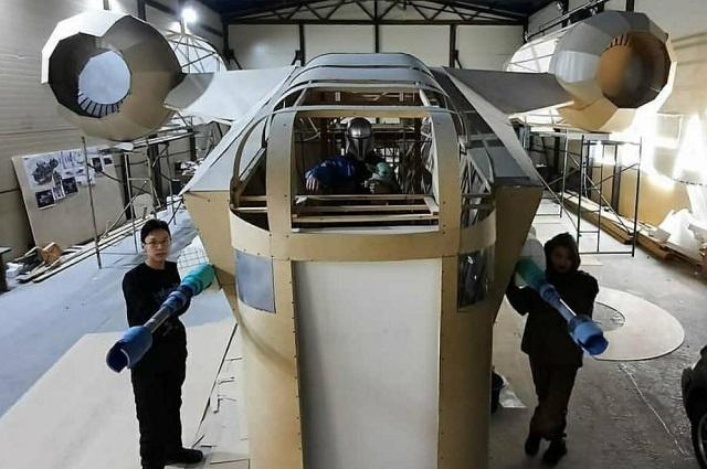 Над космическим кораблем работают пять человек.