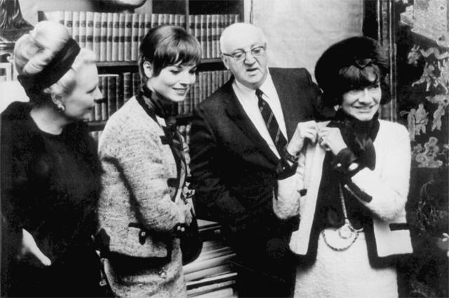 Коко Шанель показывает президенту Франции Жоржу Помпиду, его жене иитальянской кинодиве Эльзе Мартинелли, как носить золотые ожерелья, разработанныеею.