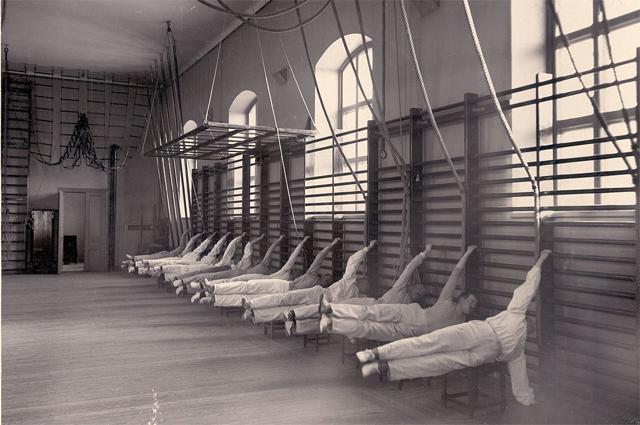 Элемент Флажок, выполняемый на шведской стенке. Центральный институт гимнастики. Около 1900 года.