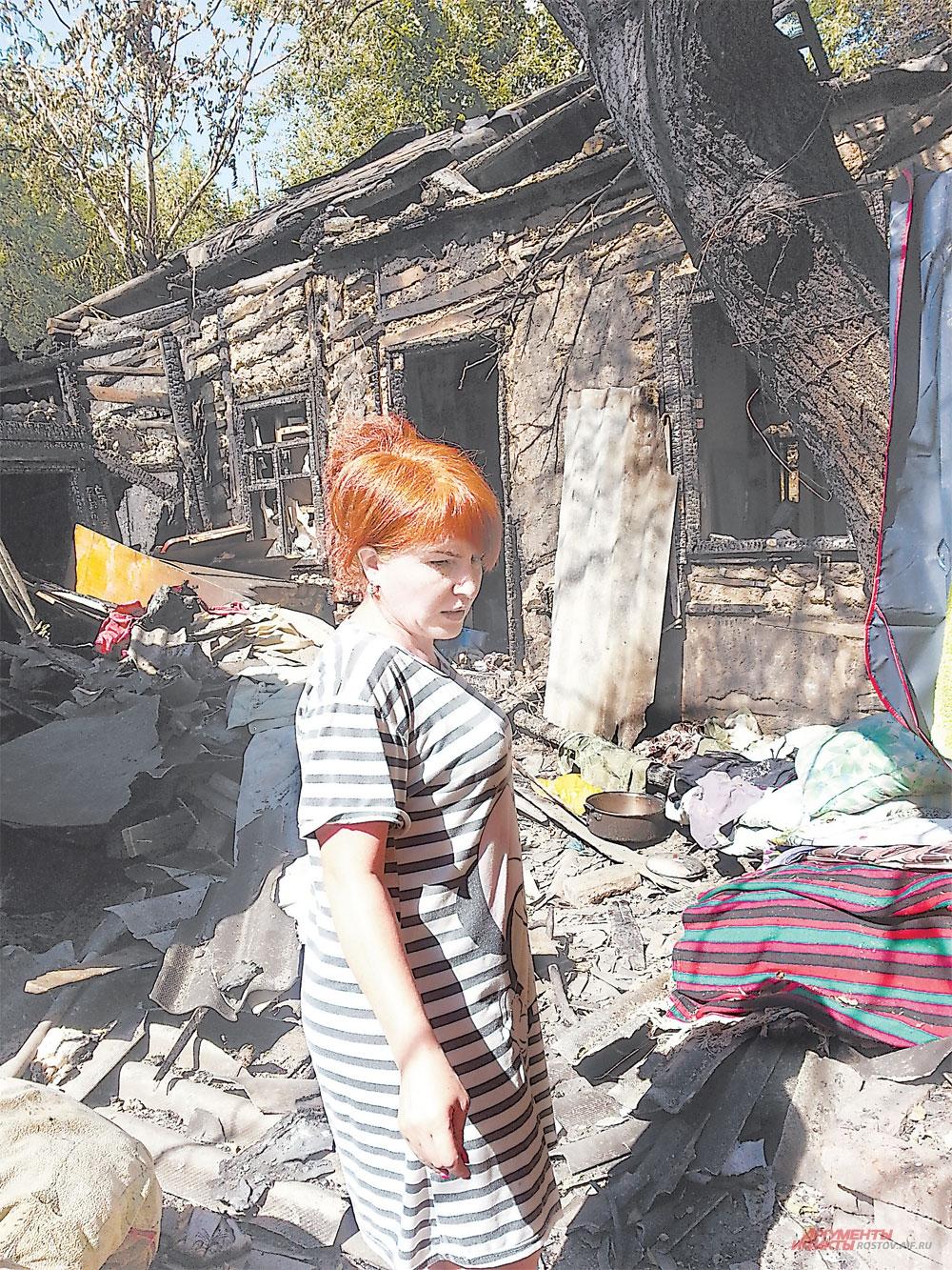 На пепелище люди пытаются найти хоть что-то уцелевшее в огне.