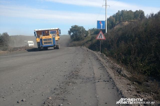 Груженные углем самосвалы ездят по одной дороге с автобусами и машинами.
