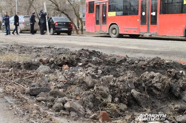 Дорожное покрытие - асфальтовая крошка, а по краям - лужи, строительный мусор и грязь