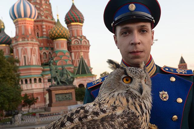 Военнослужащий орнитологической службы Кремля с филином.
