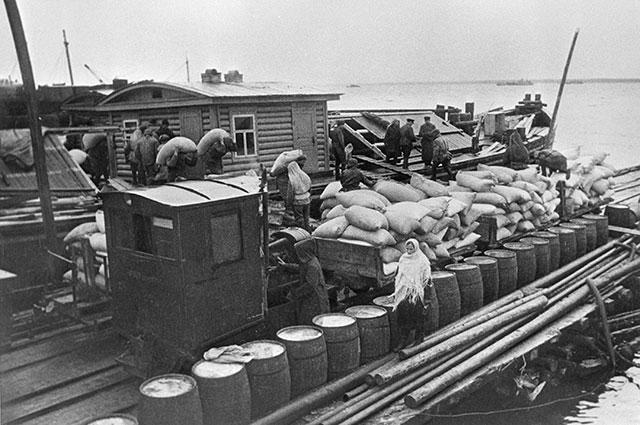 Доставка продовольствия по Ладожскому озеру на барже в осажденный Ленинград, 1942 г.