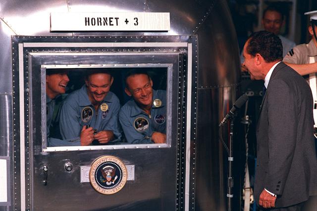 Президент Никсон общается с экипажем «Аполлона-11», находящимся в карантинном фургоне.
