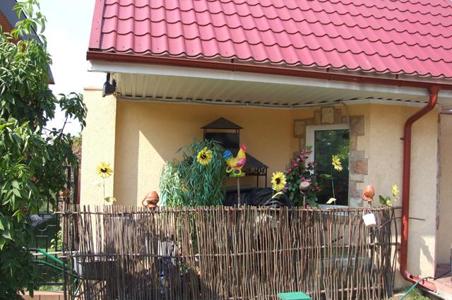 Свою нотку в экстерьер здания вносит заборчик  в деревенском стиле.