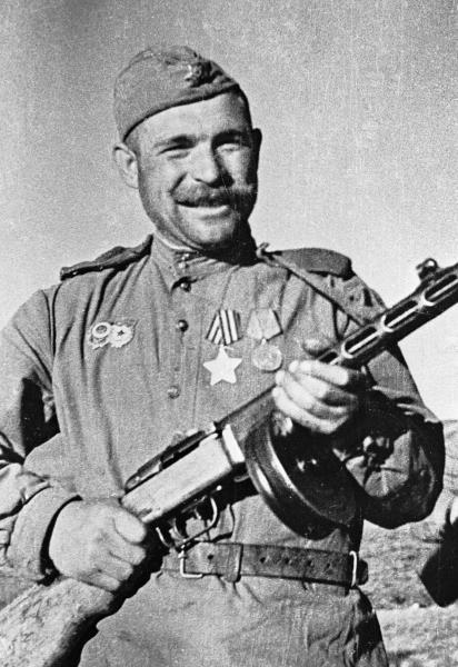 Солдат Иван Соколов стоит с пистолетом-пулеметом Шпагина в руках