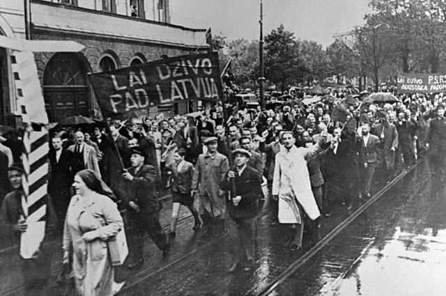 Демонстранты, идущие поулицам Риги, несут транспаранты снадписью «Даздравствует Советская Латвия».