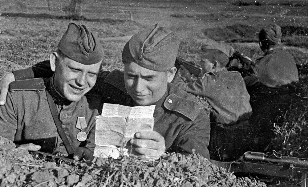 1944 год. 3-й Украинский фронт. Гвардии красноармеец В. Подрезов делится с почтальоном М. Щербаковым известиями, полученными с родины.