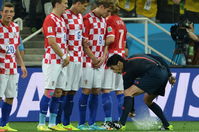 Главный судья игры Юити Нисимура наносит с помощью баллончика линию для «стенки» перед ударом со штрафного во время матча группового этапа Чемпионата мира по футболу 2014 между сборными командами Бразилии и Хорватии