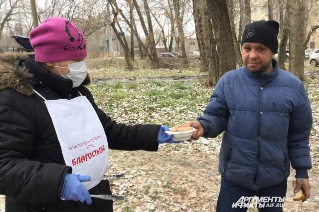 Бездомные с радостью принимают еду от волонтёров.