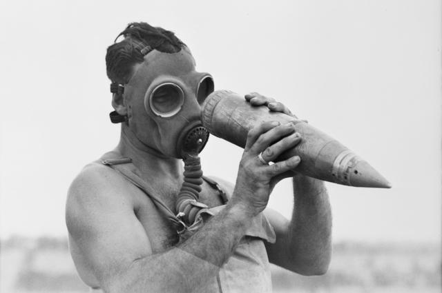 Австралийский наблюдатель в пораженной газом области осматривает неразорвавшийся снаряд.