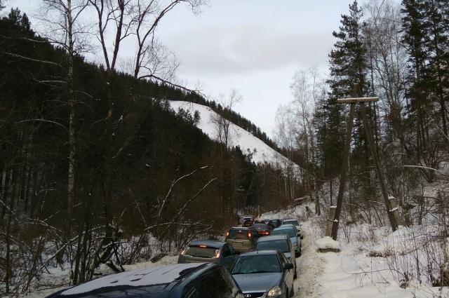 Пешеходов на узкой дороге с двух сторон вытесняет автотранспорт.
