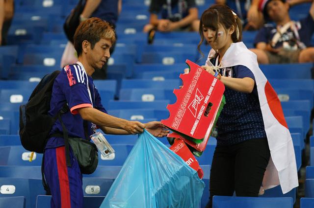 Болельщики сборной Японии убирают мусор после окончания матча.