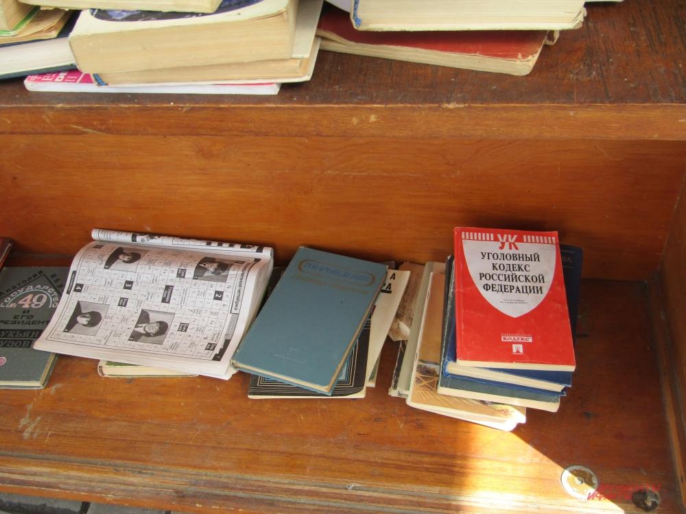 На полках книжного шкафа можно увидеть литературу совершенно разных жанров.