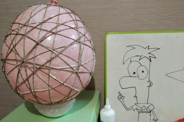 Нитку нужно обмакнуть в клей ПВА и обмотать ею шарик. Выглядит обмотанный шар вот так. Ему нужно подсохнуть.