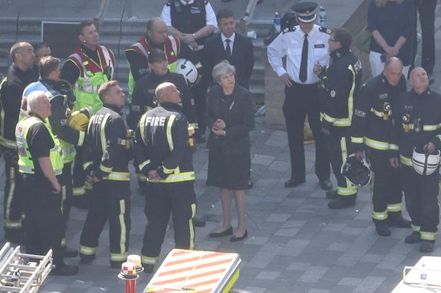 Премьер-министр Великобритании Тереза Мэй и пожарные.