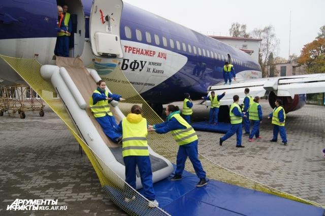 Бортпроводники отрабатывают спуск по аварийному трапу.